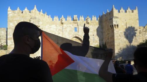 FILE - In this June 19, 2021, file photo, Palestinians demonstrators wave the Palestinian flag during protest in Damascus gate just outside Jerusalem's Old City. Palestinians and Jewish settlers hurled stones, chairs and fireworks at each other overnight in a tense Jerusalem neighborhood where settler groups are trying to evict several Palestinian families, officials said Tuesday, June 22. (AP Photo/Mahmoud Illean, File)