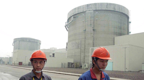 FILE - In this June 10, 2005 file photo, workers walk past a part of the Qinshan No. 2 Nuclear Power Plant, China's first self-designed and self-built national commercial nuclear power plant in Qinshan, about 125 kilometers (about 90 miles) southwest of Shanghai, China. Beijing's wants to compete with the United States, France and Russia as an exporter of atomic power technology. (AP Photo/Eugene Hoshiko, File)