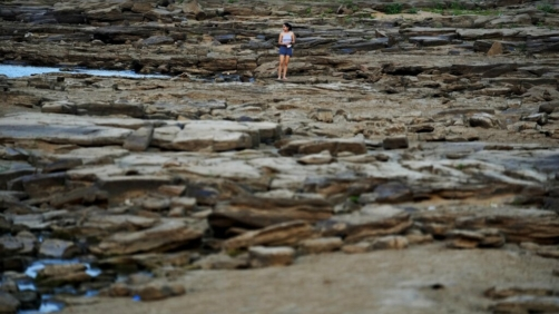 A girl walks on the exposed bed of the Paraguay River, in Villeta, Paraguay, Monday, Sept. 6, 2021, amid an ongoing drought. (AP Photo/Jorge Saenz)