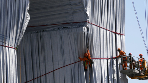 Workers put the final touch to wrap the Arc de Triomphe monument, in Paris, Thursday, Sept. 16, 2021. The