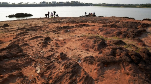 Families fish on the exposed bed of the Paraguay river, amid a historic drought that is affecting the river´s  level, in Mariano Roque Alonso, Paraguay, Monday, Sept. 20, 2021. (AP Photo/Jorge Saenz)