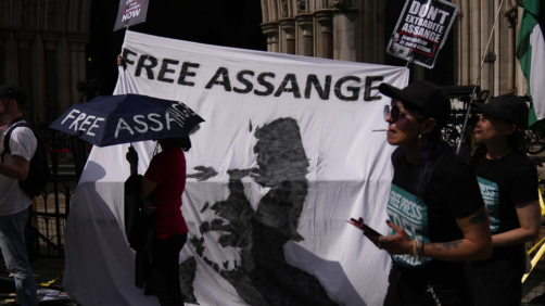 Supporters of WikiLeaks founder Julian Assange stand in front of a banner bearing an image of him, during the first hearing in the Julian Assange extradition appeal, at the High Court in London, Wednesday, Aug. 11, 2021. Lawyers acting on behalf of the U.S. government on Wednesday challenged a British judge's decision to block the extradition of WikiLeaks founder Julian Assange to face espionage charges in the United States, arguing that assessments of Assange's mental health should be reviewed. (AP Photo/Matt Dunham)