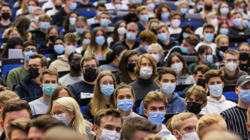 Students wear mouth-to-nose coverings while sitting close to each other during the lecture