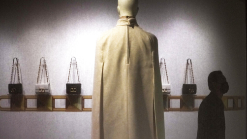 A man wearing a face mask walks by the Valentino collection on display at Valentino Re-Signify Exhibition held at a shopping mall in Beijing, Thursday, Oct. 21, 2021. (AP Photo/Andy Wong)