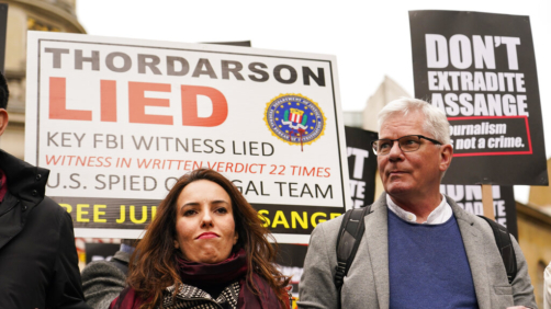 Julian Assange's partner Stella Morris, left, and Wikileaks editor-in-chief Kristin Hrafnsson hold placards and take part in a march in London, Saturday, Oct. 23, 2021, ahead of next week's extradition case appeal. (AP Photo/Alberto Pezzali)