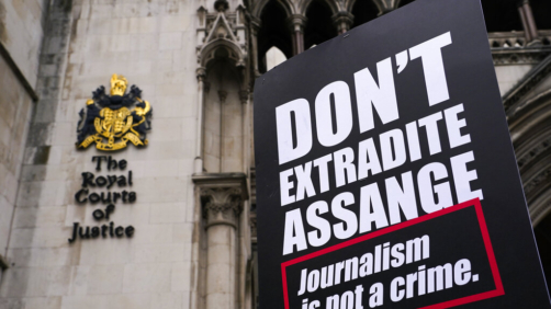 A placard in support WikiLeaks founder Julian Assange is held the Royal Courts of Justice, in London, Saturday, Oct. 23, 2021, ahead of next week's extradition case appeal. (AP Photo/Alberto Pezzali)