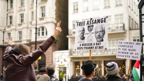 Supporters of WikiLeaks founder Julian Assange hold placards as they gather outside the Royal Courts of Justice, in London, Saturday, Oct. 23, 2021, ahead of next week's extradition case appeal. (AP Photo/Alberto Pezzali)