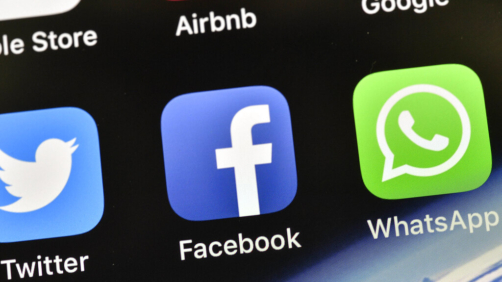 FILE - In this Nov. 15, 2018 file photo, the icons of Facebook and WhatsApp are pictured on an iPhone, in Gelsenkirchen, Germany. Last spring, as false claims about vaccine safety threatened to undermine the world's response to COVID-19, researchers at Facebook wrote that they could reduce vaccine misinformation by tweaking how vaccine posts show up on users' newsfeeds, or by turning off comments entirely. Yet despite internal documents showing these changes worked, Facebook was slow to take action. (AP Photo/Martin Meissner, File)